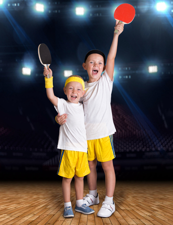 Twee broers spelen tennis in de sportzaal. Kampioenen. Stockfoto - 84549059