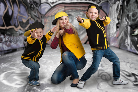 A young mother and two young sons in the style of a hip hop. Fashionable family. Graffiti on the walls.
