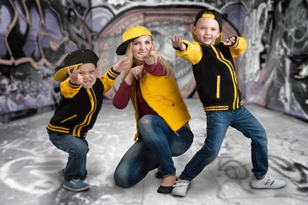 Une jeune mère et deux jeunes fils dans le style d'un hip-hop. Famille à la mode. Graffiti sur les murs. Banque d'images - 85334799