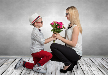 Small son gives his beloved mother a beautiful bouquet of pink roses. Spring, concept of family vacation. Women's day, mother's day.