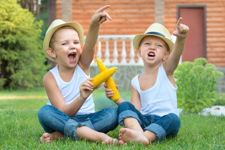 Two brothers sitting on the grass and eating corn on the cob in the garden. Fun games, laughter.
