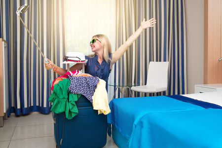 A young woman examines a suitcase on vacation.Selfie happy camper. Stock Photo