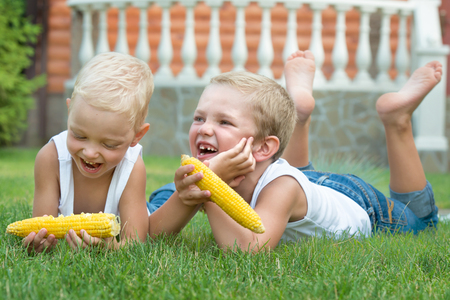 Two brothers lying on the grass and eat corn on the cob in the garden