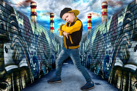 The little boy in the style of Hip-Hop. Children's fashion.Cap and jacket. A Small Rapper.Graffiti on the walls.Cool rap DJ. Stock Photo - 85318060