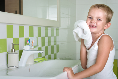 sink: A boy washes his face, wipes her face with a towel in the bathroom.