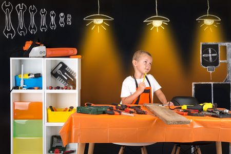 Boy working in his fathers carpentry workshop. Stock Photo