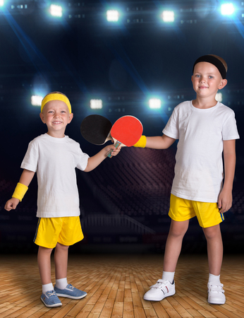 Two brothers play tennis in the sports hall.Champions. Banco de Imagens
