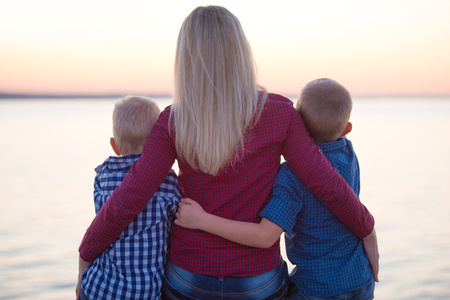 Mother and two sons walk on the promenade and watch the sunset Banco de Imagens