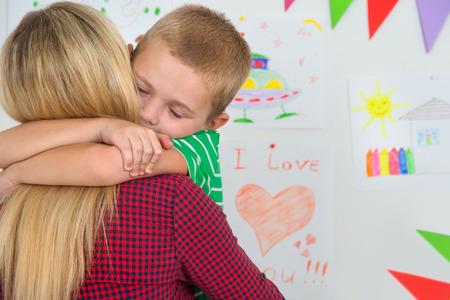 tenderly: Cute boy tenderly hugging his beloved mother.