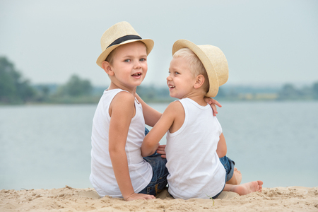 Two brothers relaxing on the beach of the lake. Imagens