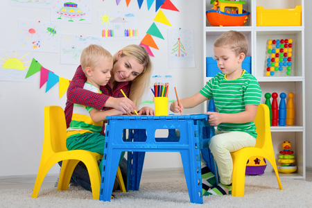 Children with mom and draw pictures in the kids room. Banco de Imagens