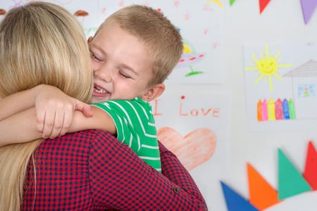 Cute boy tenderly hugging his beloved mother.