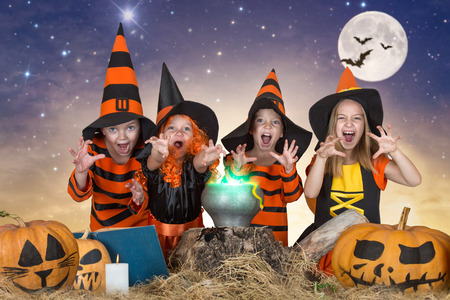 Halloween.The children of witches and wizards cooking potion in the cauldron with pumpkin and spell book. Stock Photo