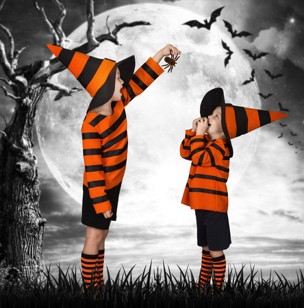 Halloween.Two brothers in costume walking in a scary woods. Scare each other with scary spiders Stock Photo