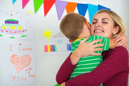 Cute boy tenderly hugging his beloved mother. Imagens