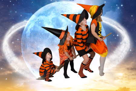 Halloween.The children of witches and wizards fly on broomsticks across the sky.Beautiful children in Halloween costumes.