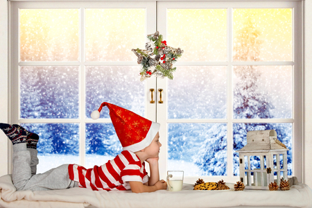 Merry Christmas and happy holidays! A small child resting, sitting on the window waiting for Santa.