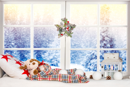 Merry Christmas and Happy Holidays! Christmas decor in the window, toy dog ??sleeps on a pillow under a blanket. Stock Photo