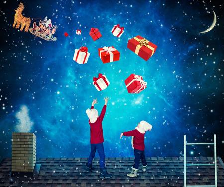Prettige kerstdagen en een fijne vakantie! Kinderdozen met geschenken van Santa.Santa gooiden cadeautjes naar kleine kinderen op het dak van het huis. Stockfoto