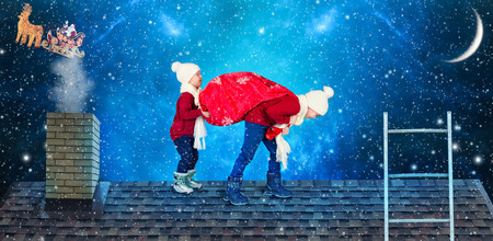 Merry Christmas! Children carrying a bag of gifts from Santa. Santa dropped a sack of presents to small children on the roof of the house. Stock Photo