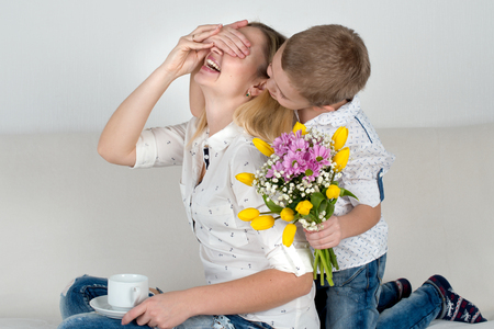 Son holding his bouquet of beautiful flowers for his beloved mother.The concept of the celebration, women's day. Stockfoto