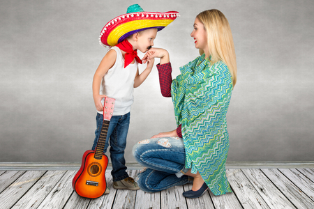 A small boy in a sombrero kisses moms hand.Son plays the guitar and sings a serenade for his mother. Stock Photo