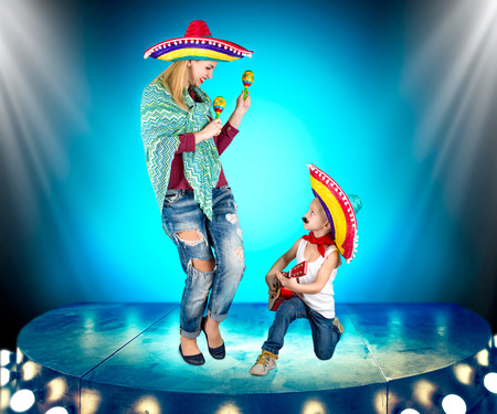 Mexican party. A small boy in a sombrero plays the guitar and sings a serenade for his mother.