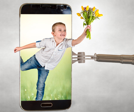 Spring surprise. The boy gives a bouquet of tulips through the phone screen. The concept of the holiday.