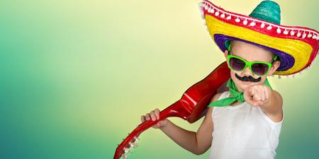 Fête mexicaine. Garçon avec une fausse moustache dans un sombrero jouant de la guitare.