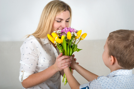 Son gives his beloved mother a beautiful bouquet of tulips. The concept of the celebration, women's day.