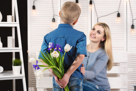 Son congratulates his beloved mother and gives her a bouquet of tulips.The concept of the celebration, women's day.Mother's Day.