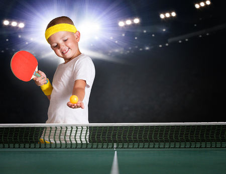 Portrait of a child boy playing ping-pong.