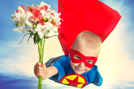 A child in a superhero costume with a bouquet of flowers.