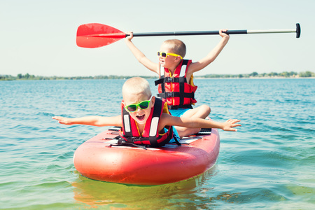Two brothers swimming on stand up paddle board.Water sports, active lifestyle.