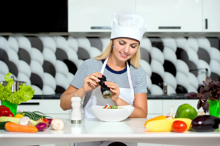 Young Woman Cooking in the kitchen. Healthy Food - Vegetable Salad. Diet. Healthy Lifestyle. Cooking At Home. Banque d'images