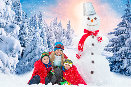 A family in a winter snowy forest mold a big snowman.Family winter fun for Christmas vacation. Imagens