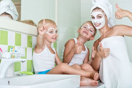 Mother and children make a face mask in the morning.The boys joke with mom. Beauty treatments for the skin