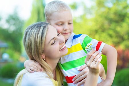 The little son gives his mother a bouquet of daisies.