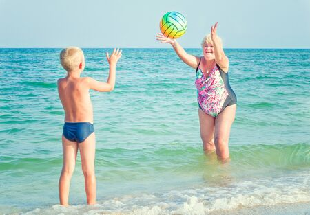 Grandmother with grandson on beach playing ball.