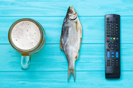 Vacation concept. A mug of cold beer with dried fish and a TV remote.
