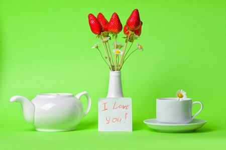 Berry bouquet. A bouquet of strawberries in a white vase and a small card on a green background. Cup of tea with chamomile and teapot.