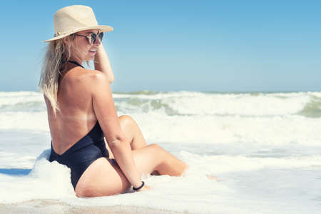 Young sexy woman in black swimsuit and straw hat sunbathes and relaxes on the beach.