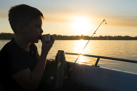 The boy is drinking tea from a cup while fishing.
