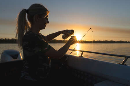 A woman is drinking tea from a cup while fishing. Fishing on the lake from a boat. Fishing rods in sunlight. Fishing rest concept.