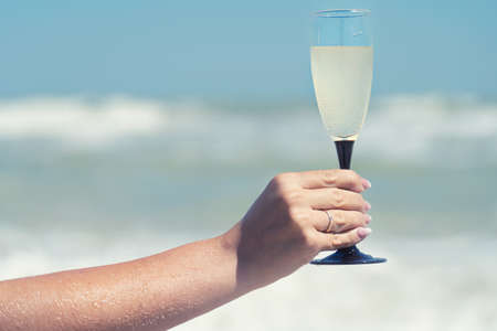 Glass of champagne on the seashore.