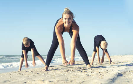 Mother and children do exercises on the beach, they meet the sunrise. Fitness, sport, yoga and healthy lifestyle concept.
