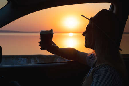A young woman drinks coffee and looks out the car window at the sunset on the sea.