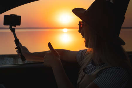 Young woman looking out car window of the sunset on the sea and and photographed on the phone.