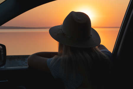 A young woman looks out the car window at the sunset on the sea.
