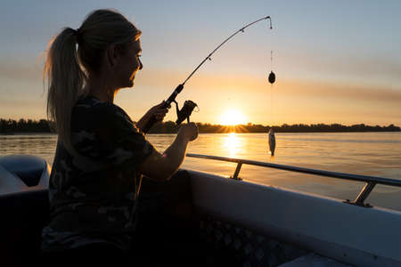 A woman on a fishing trip caught a fish.Fishing on the lake from a boat. Fishing rods in sunlight. Fishing rest concept.